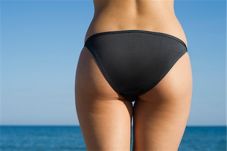 Woman in bikini at the beach, cropped rear view Stock Photo - Premium Royalty-Free, Code: 632-05554215