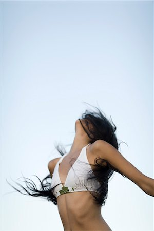 release - Woman in bikini throwing head back, hair covering face Stock Photo - Premium Royalty-Free, Code: 632-05553424