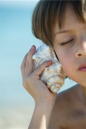 dreamy - Boy listening to seashell with eyes closed Stock Photo - Premium Royalty-Free, Code: 632-05553592