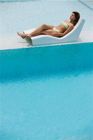 Young woman sunbathing by pool Stock Photo - Premium Royalty-Free, Code: 632-05553656