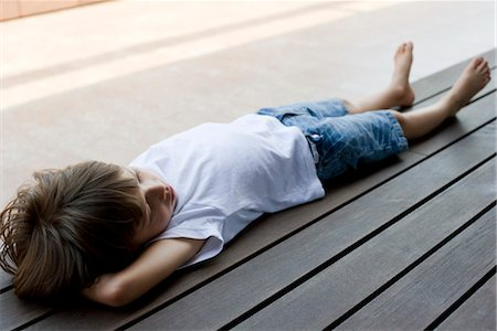 Little boy lying on back on deck Stock Photo - Premium Royalty-Free, Code: 632-05553743