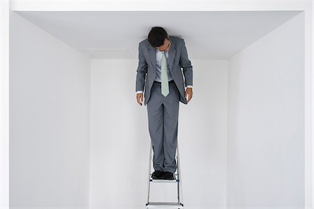 restrained - Executive standing on stepladder Stock Photo - Premium Royalty-Free, Code: 632-05604172