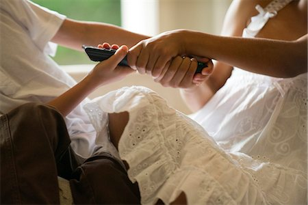 Children fighting over remote control, cropped Stock Photo - Premium Royalty-Free, Code: 632-05604234