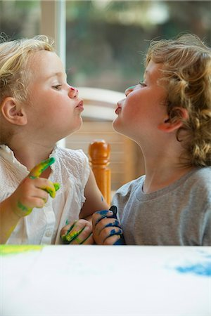 people kissing little boys - Little girl and boy looking at each other and puckering lips Stock Photo - Premium Royalty-Free, Code: 632-05604276