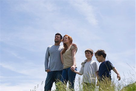 Parents and two boys standing on meadow holding hands, low angle view Stock Photo - Premium Royalty-Free, Code: 632-05604294