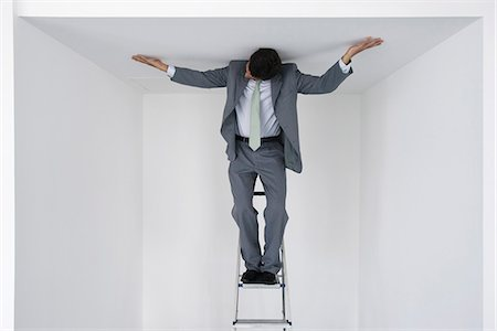 restrained - Executive standing on stepladder, arms outstretched on ceiling Stock Photo - Premium Royalty-Free, Code: 632-05604359