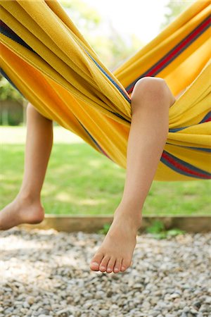 Child's legs dangling from hammock Stock Photo - Premium Royalty-Free, Code: 632-05604393