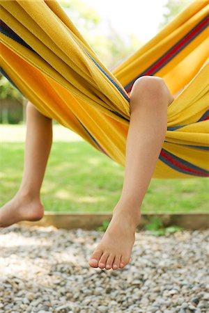 Child's legs dangling from hammock Stock Photo - Premium Royalty-Free, Code: 632-05604393