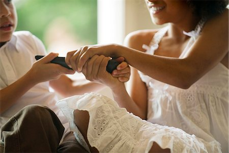 Children fighting over remote control, cropped Stock Photo - Premium Royalty-Free, Code: 632-05604486