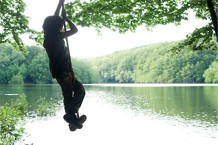 swing (sports) - Boy standing on swing by lake Stock Photo - Premium Royalty-Free, Code: 632-05604494