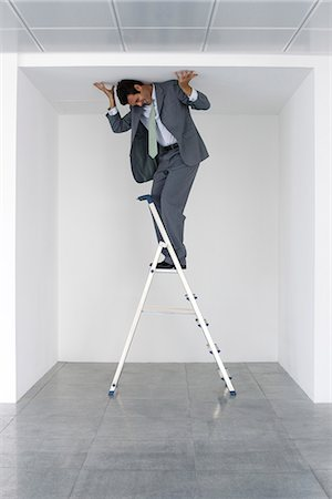 restrained - Executive standing on stepladder, pushing ceiling Stock Photo - Premium Royalty-Free, Code: 632-05604583