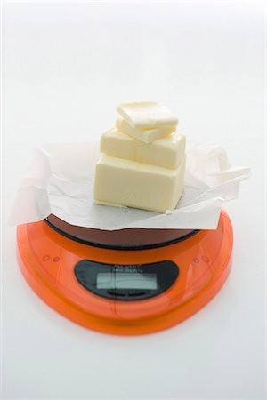 Weighing butter on kitchen scale Stock Photo - Premium Royalty-Free, Code: 632-05603865