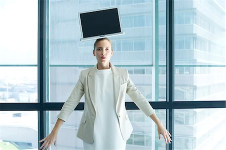Businesswoman with laptop computer on head Stock Photo - Premium Royalty-Free, Code: 632-05603933