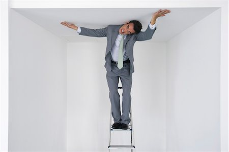 restrained - Executive standing on stepladder, pushing ceiling Stock Photo - Premium Royalty-Free, Code: 632-05603993