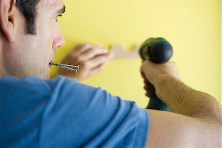 drilling - Man using power drill, biting screws in mouth Stock Photo - Premium Royalty-Free, Code: 632-05759482