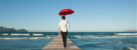 Man walking on pier with umbrella, rear view Stock Photo - Premium Royalty-Free, Code: 632-05759616