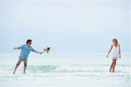 Couple walking apart in sea, man holding out bouquet Stock Photo - Premium Royalty-Free, Code: 632-05759725