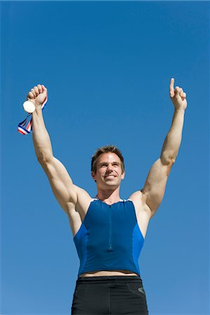 Male athlete holding up gold medal Stock Photo - Premium Royalty-Free, Code: 632-05759814
