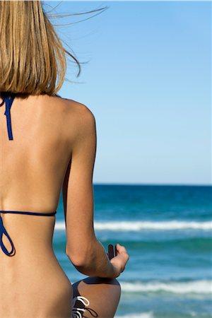 Woman in bikini sitting in lotus position, rear view Stock Photo - Premium Royalty-Free, Code: 632-05759818