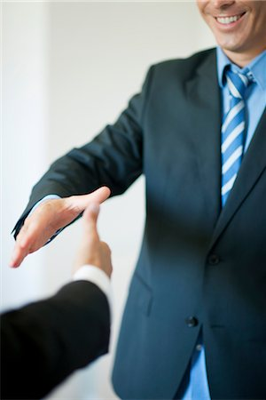Executives extending hands to shake, cropped Stock Photo - Premium Royalty-Free, Code: 632-05759810