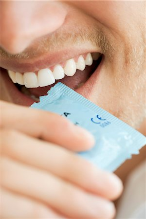 Man opening condom wrapper with his teeth, cropped Stock Photo - Premium Royalty-Free, Code: 632-05759839