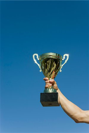 Man's arm holding up trophy Stock Photo - Premium Royalty-Free, Code: 632-05759870