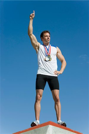 Male athlete standing on winner's podium with hand raised in victory Stock Photo - Premium Royalty-Free, Code: 632-05760039