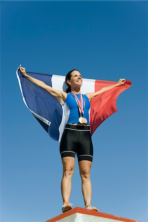 Female athlete on winner's podium, holding up French flag Stock Photo - Premium Royalty-Free, Code: 632-05760060