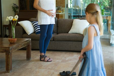 Daughter helping pregnant mother vacuum floor, cropped Stock Photo - Premium Royalty-Free, Code: 632-05760062
