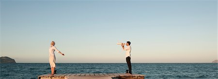 Couple standing on pier, man talking to woman through megaphone Stock Photo - Premium Royalty-Free, Code: 632-05760118