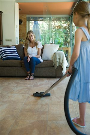 Woman sitting on sofa smiling, daughter vacuuming floor in foreground Stock Photo - Premium Royalty-Free, Code: 632-05760168
