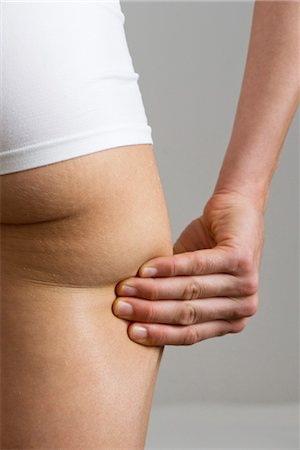 Woman pinching own buttock, cropped Stock Photo - Premium Royalty-Free, Code: 632-05760323