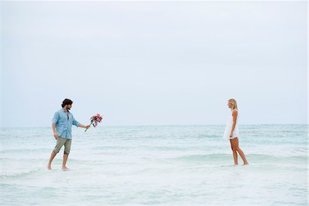 Couple walking on water towards each other, man holding out bouquet Stock Photo - Premium Royalty-Free, Code: 632-05760531