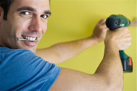 drilling - Man using power drill, biting screw in mouth Stock Photo - Premium Royalty-Free, Code: 632-05760684