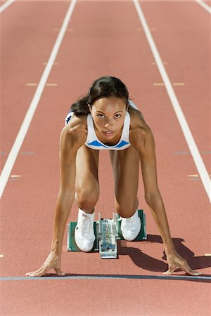 Woman crouched in starting position on running track Stock Photo - Premium Royalty-Free, Code: 632-05816050