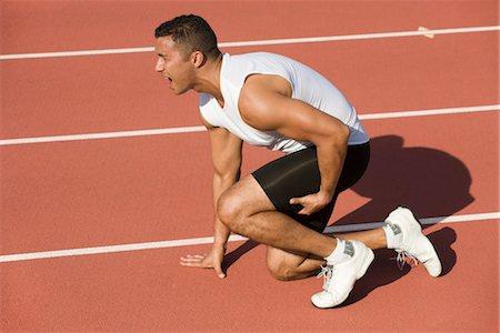 Injured runner kneeling on running track Stock Photo - Premium Royalty-Free, Code: 632-05816161