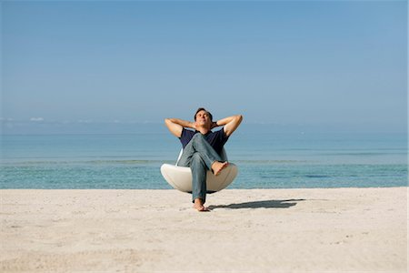 Mid-adult man relaxing in armchair on beach with eyes closed Stock Photo - Premium Royalty-Free, Code: 632-05816289