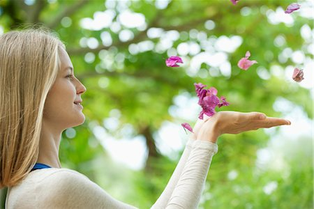 Young woman catching falling petals, side view Stock Photo - Premium Royalty-Free, Code: 632-05816357