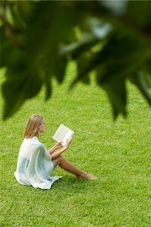 Young woman sitting on grass reading book, high angle view Stock Photo - Premium Royalty-Free, Code: 632-05816376
