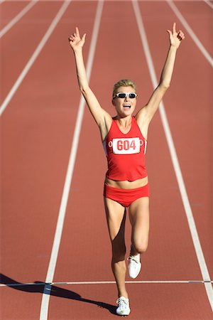 finish line - Woman running on track with arms raised in victory Stock Photo - Premium Royalty-Free, Code: 632-05816489