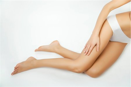 Woman touching her bare leg, cropped Stock Photo - Premium Royalty-Free, Code: 632-05816549