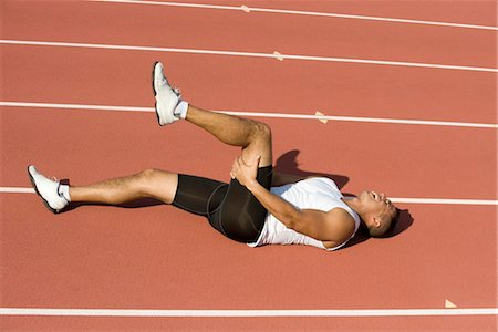 Injured runner lying on running track Stock Photo - Premium Royalty-Free, Code: 632-05816626