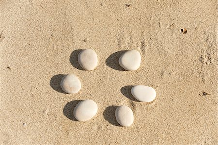 Pebbles arranged in circle on sand Stock Photo - Premium Royalty-Free, Code: 632-05816691