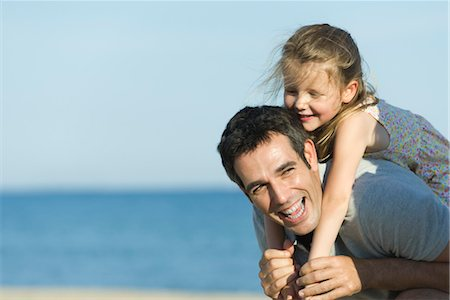 Father giving young daughter piggyback ride Stock Photo - Premium Royalty-Free, Code: 632-05816704