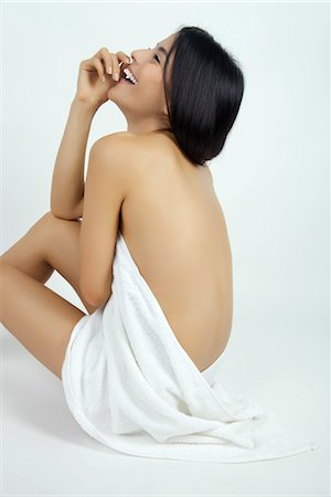 Nude woman partially covered with towel, looking up in laughter Stock Photo - Premium Royalty-Free, Code: 632-05816725