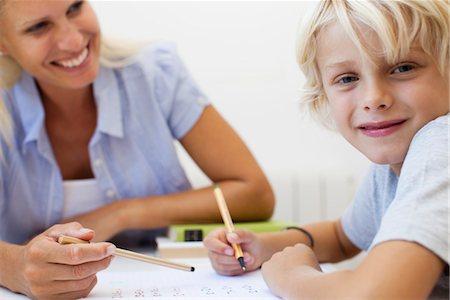 Boy doing homework, smiling at camera Stock Photo - Premium Royalty-Free, Code: 632-05816761
