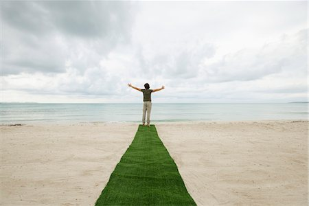 Man standing at end of carpet on beach with arms outstretched, rear view Stock Photo - Premium Royalty-Free, Code: 632-05816824