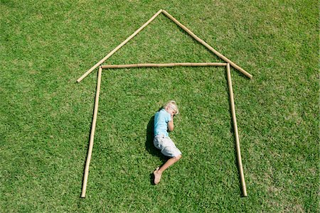 stick - Boy lying on grass within outline of house, high angle view Stock Photo - Premium Royalty-Free, Code: 632-05816839
