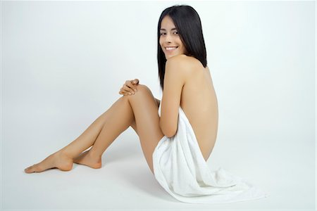 Nude woman partially covered with towel, smiling over shoulder at camera Stock Photo - Premium Royalty-Free, Code: 632-05816859