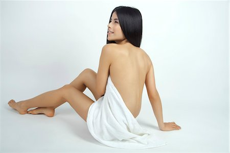 Nude woman partially covered with towel, rear view Stock Photo - Premium Royalty-Free, Code: 632-05816885
